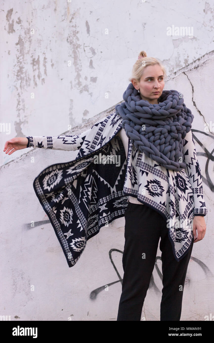 Blonde young beautiful fashion girl wearing aztec black and white jacket and knitted grey vest scarf. Festival outfit. Lifestyle street fashion trend - Stock Image