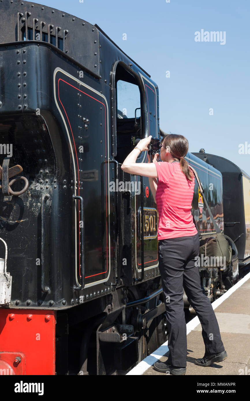 Excited female train enthusiast taking photographs of shiny, preserved steam locomotive, stationary on platform, on a gloriously sunny morning in May. - Stock Image