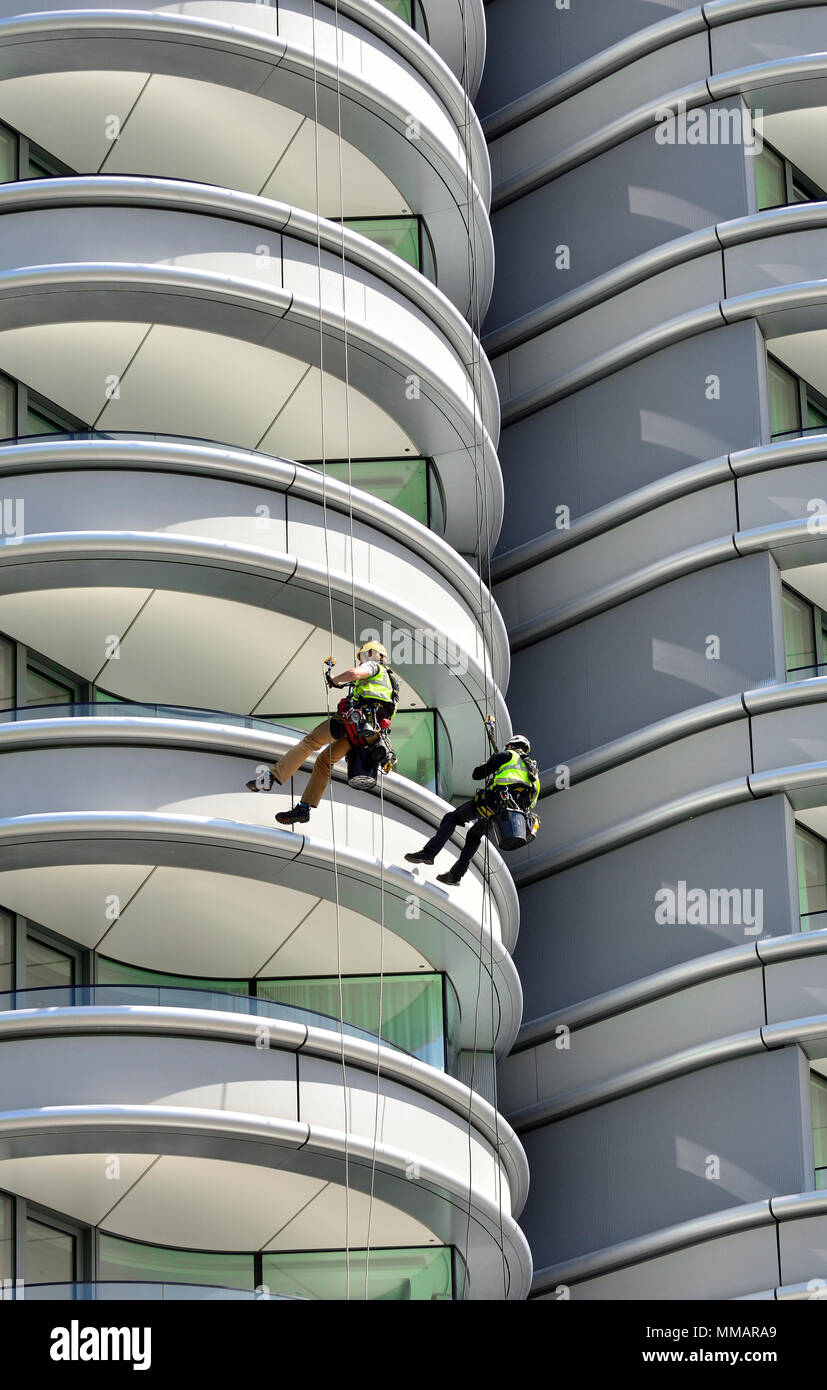 London,England, UK. Maintenance workers abseiling down the building 'The Corniche' apartments on Albert Embankment, Vauxhall Stock Photo