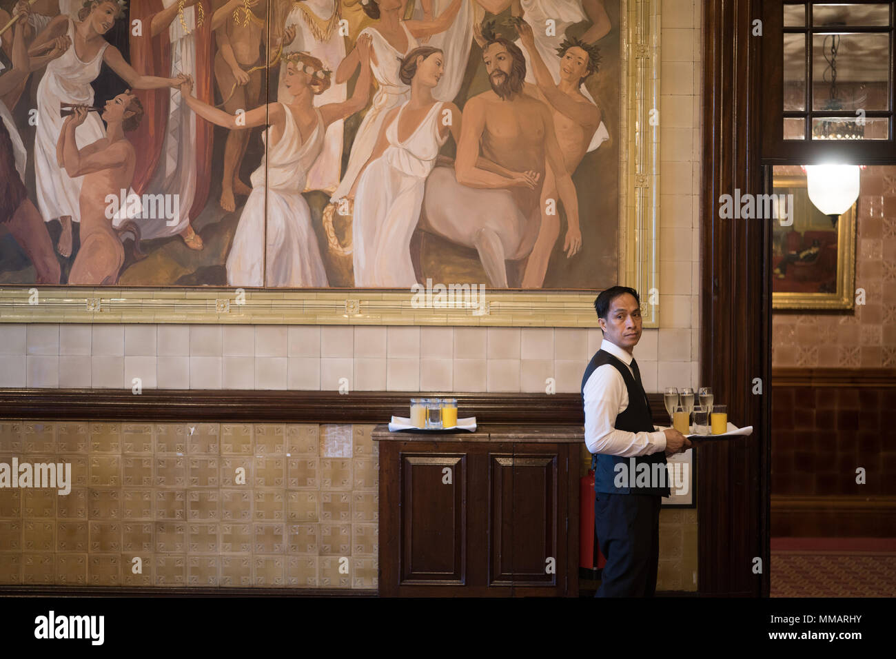 A waiter serving drinks in the dining room on the third floor of the National Liberal Club at 1 Whitehall Place in Westminster, London. Photo date: Sa - Stock Image