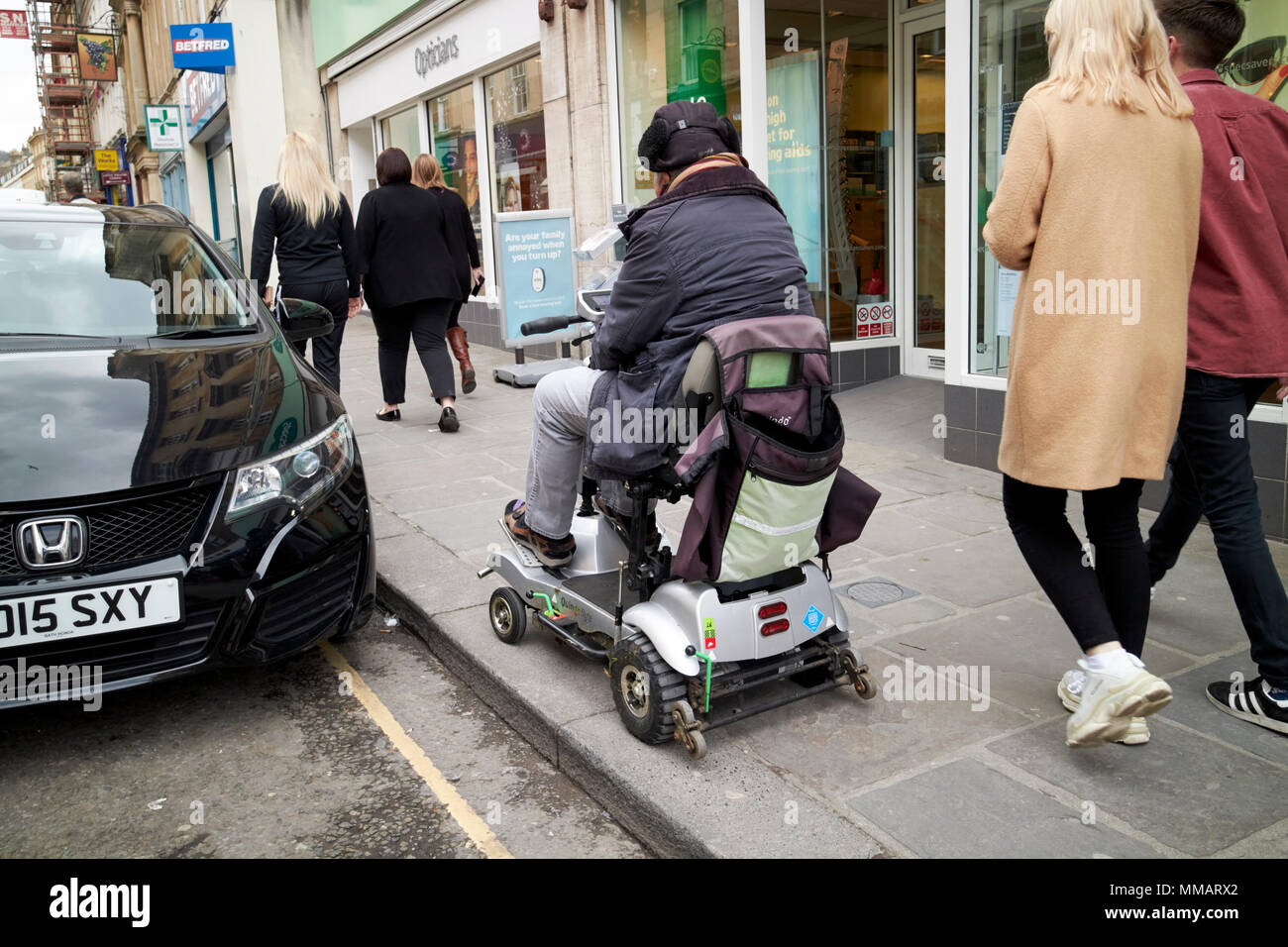 man rides disability scooter on pavement in city centre Bath England UK - Stock Image