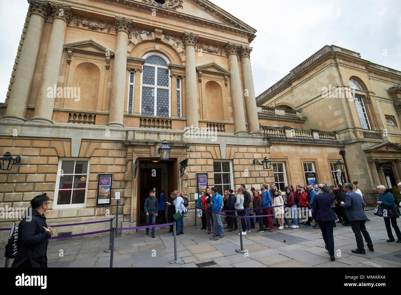 queues of tourists waiting in line to enter the roman baths complex abbey churchyard Bath England UK - Stock Image