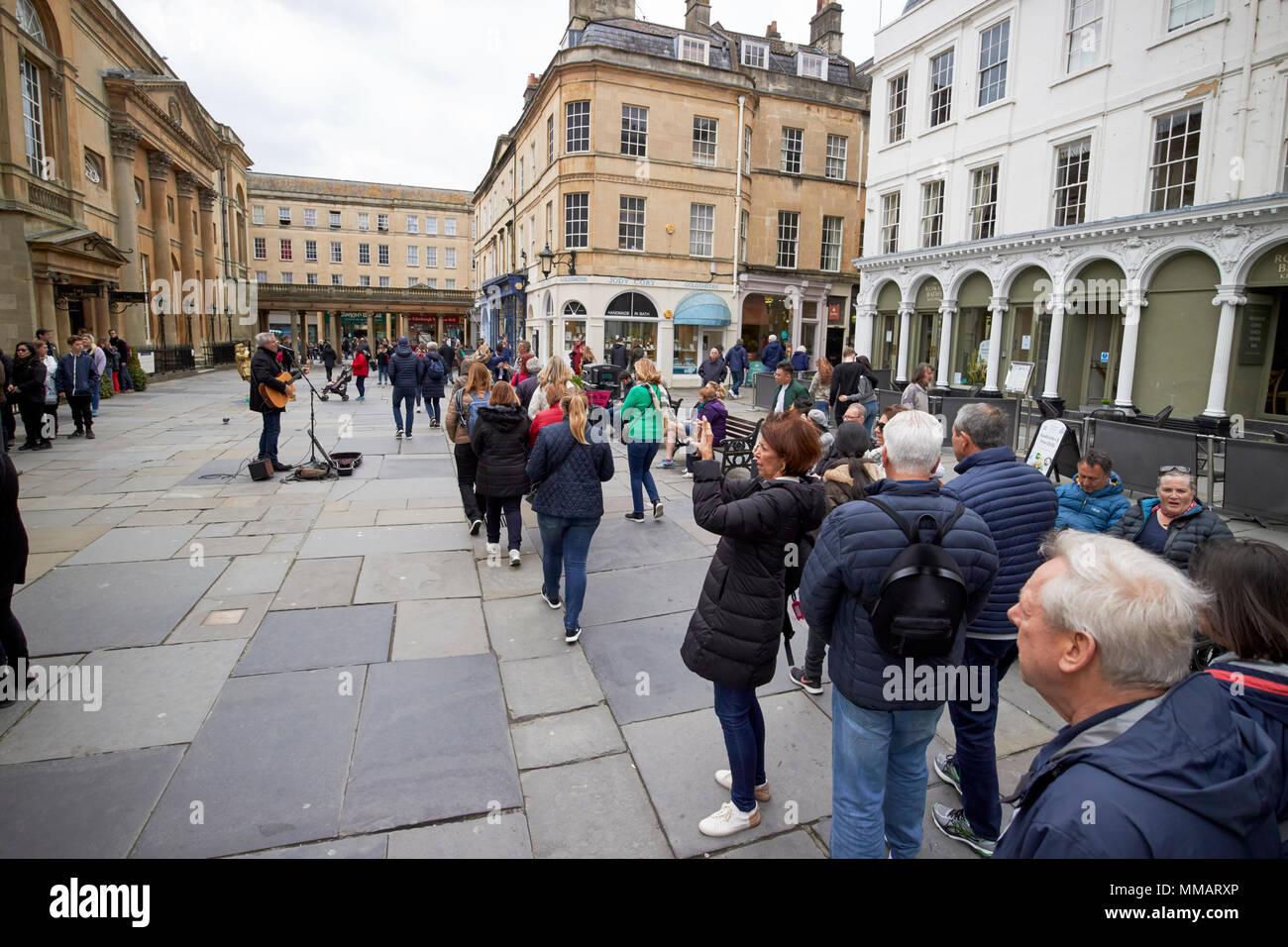 tourists on walking tour of bath walk through abbey churchyard Bath England UK - Stock Image
