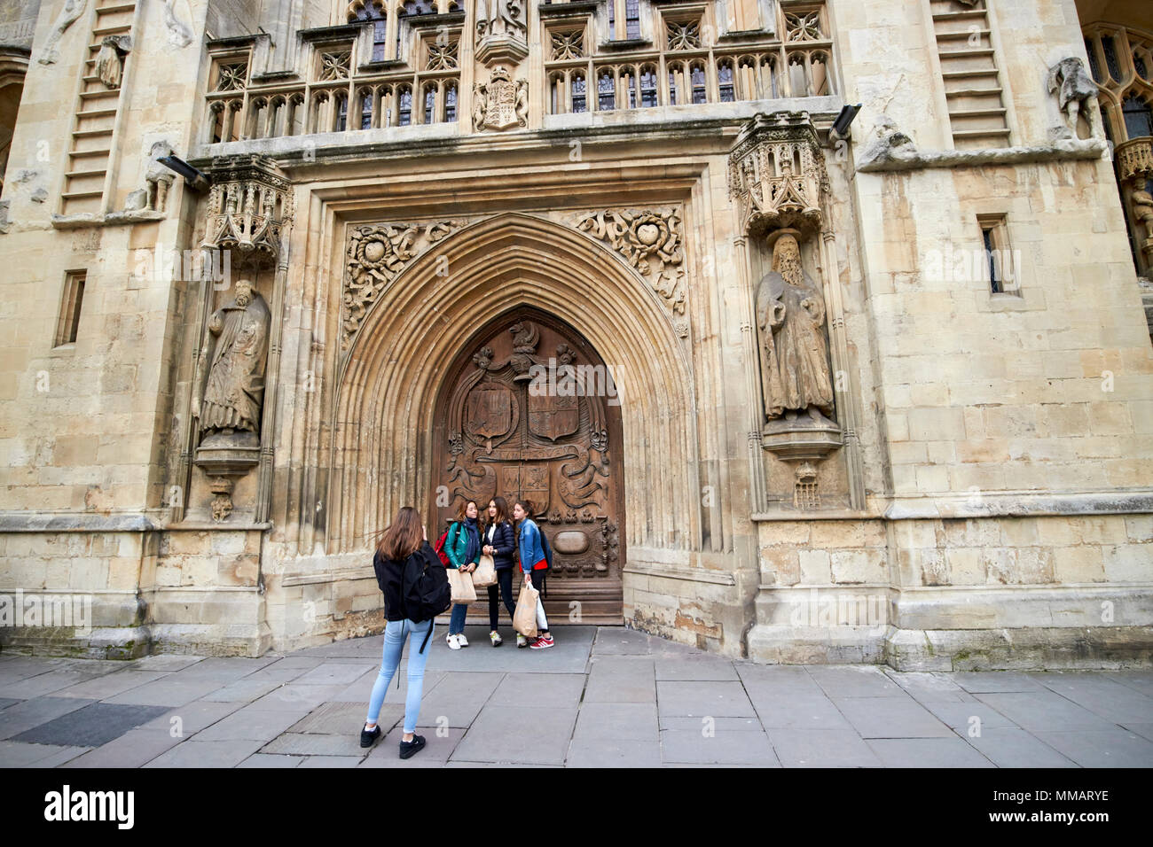 female students pose in front of large carved west front door of Bath Abbey Bath England UK Stock Photo