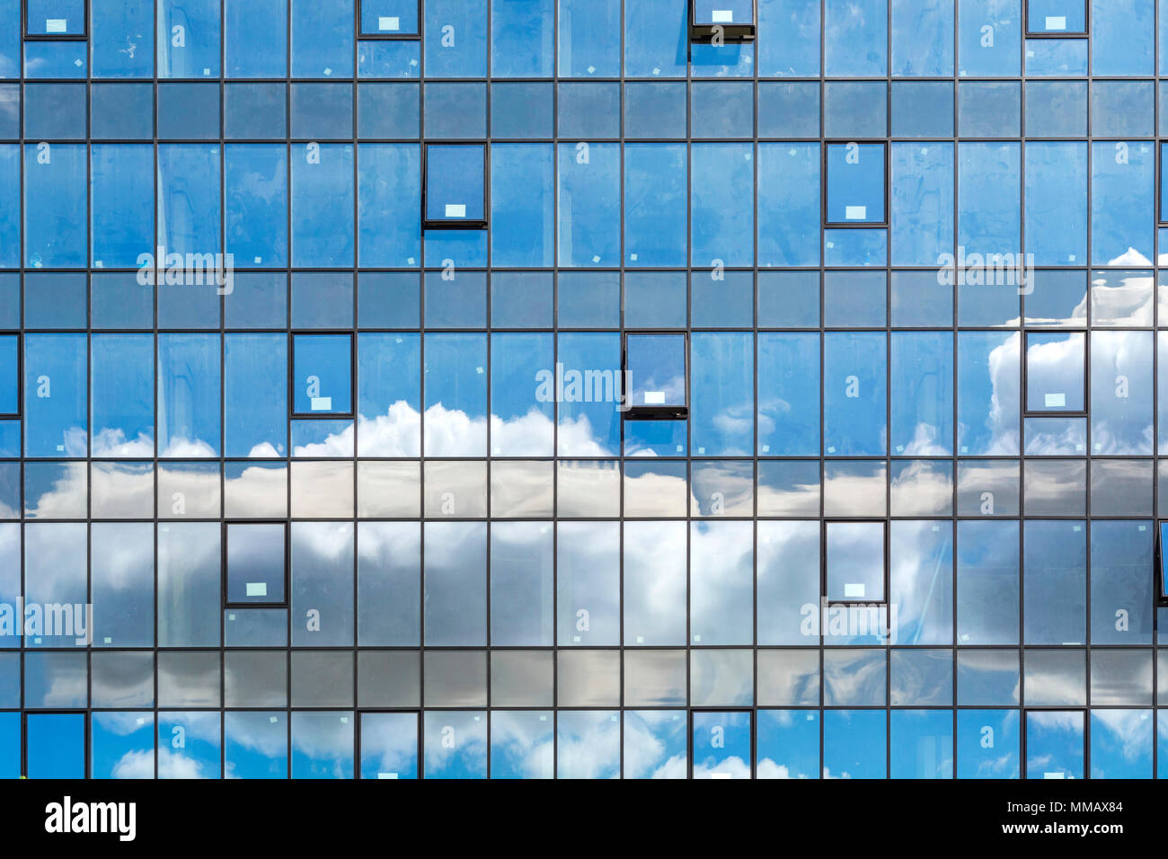 Cloudy sky reflected in the windows of modern office building. Urban abstract background Stock Photo