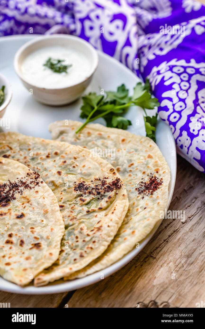 Azerbaijani traditional cuisine. Vertical shot of qutabs -flatbread with greens. Served with yogurt in white ceramic plate. - Stock Image