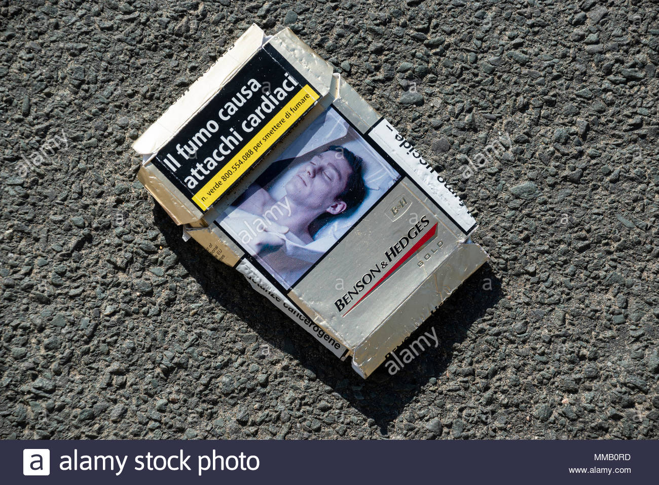 Discarded cigarette packet with the wording Il Fumo Causa Attacchi Cardiaci, Dorset, England, UK - Stock Image