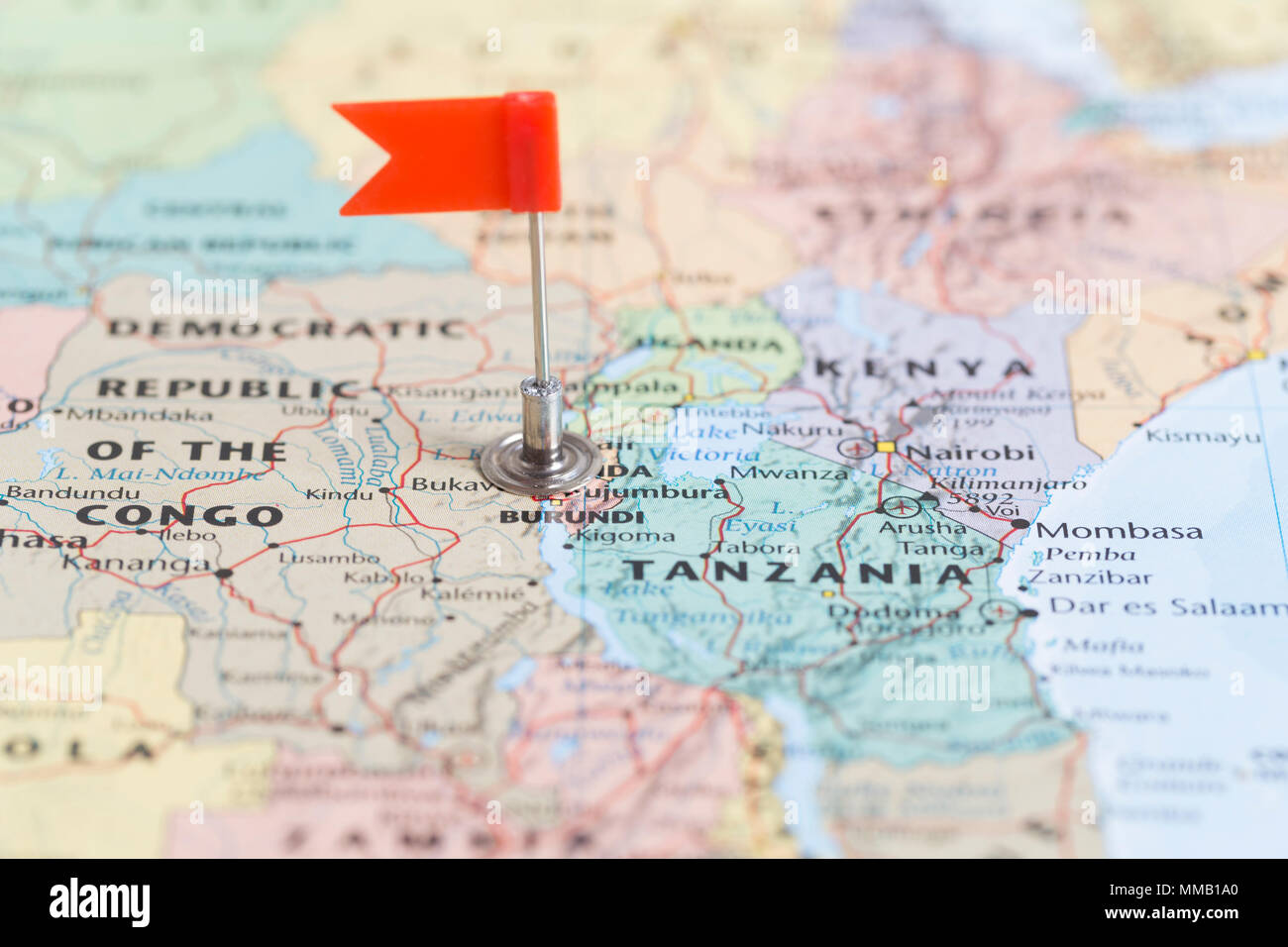 Small red flag marking the African country of Burundi on a world map. - Stock Image