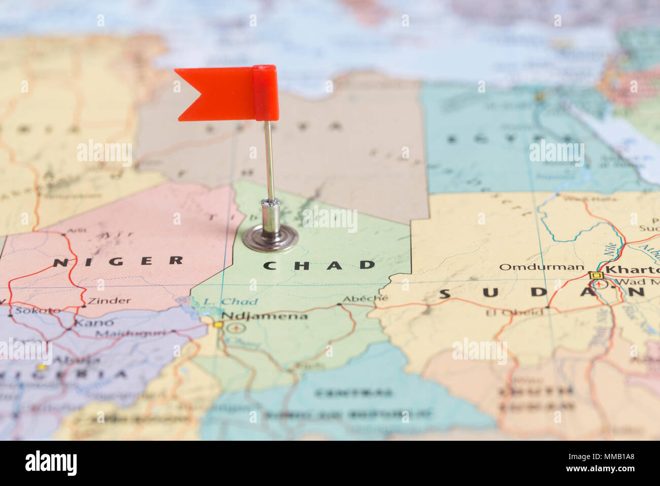 Small red flag marking the African country of  Chad on a world map. - Stock Image
