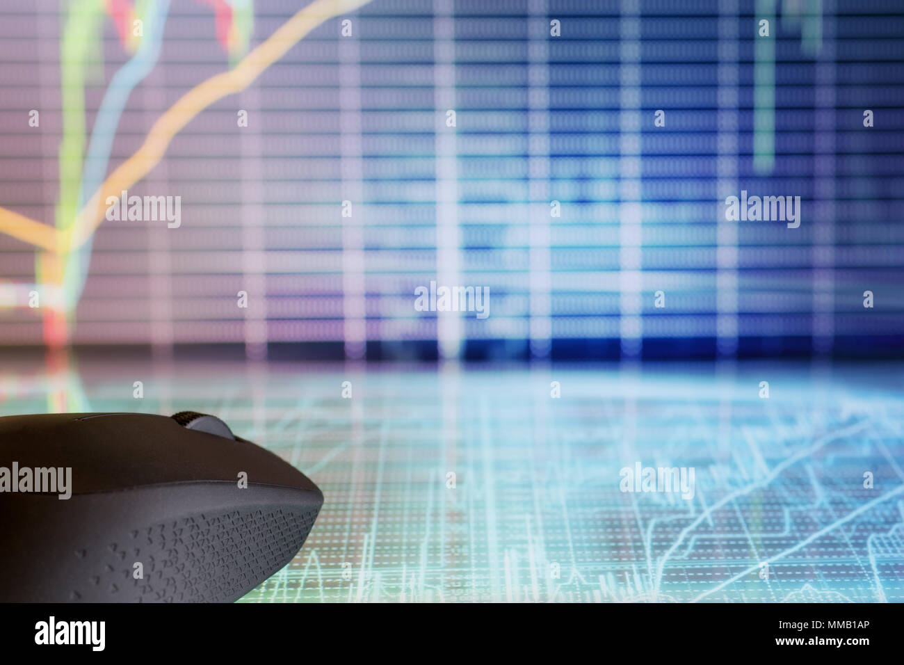 Computer mouse on futuristic display with defocused stock market graphs. Internet trading and modern business theme - Stock Image