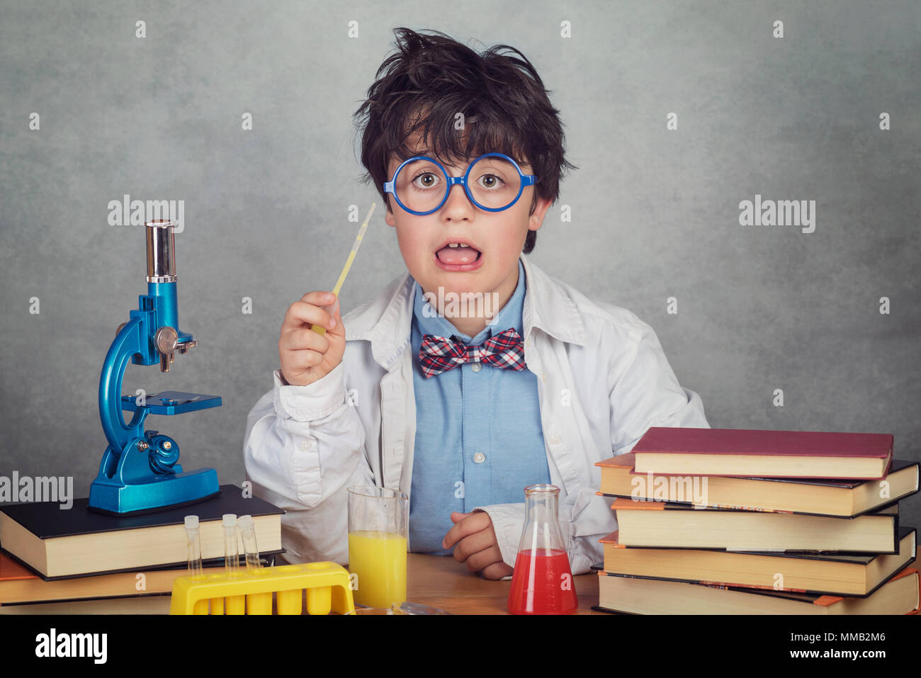 boy is making science experiments in a laboratory on gray background - Stock Image
