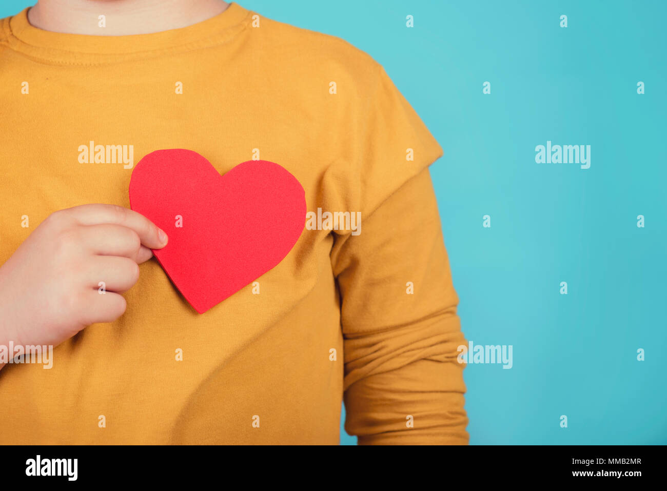 boy with a heart on blue background - Stock Image