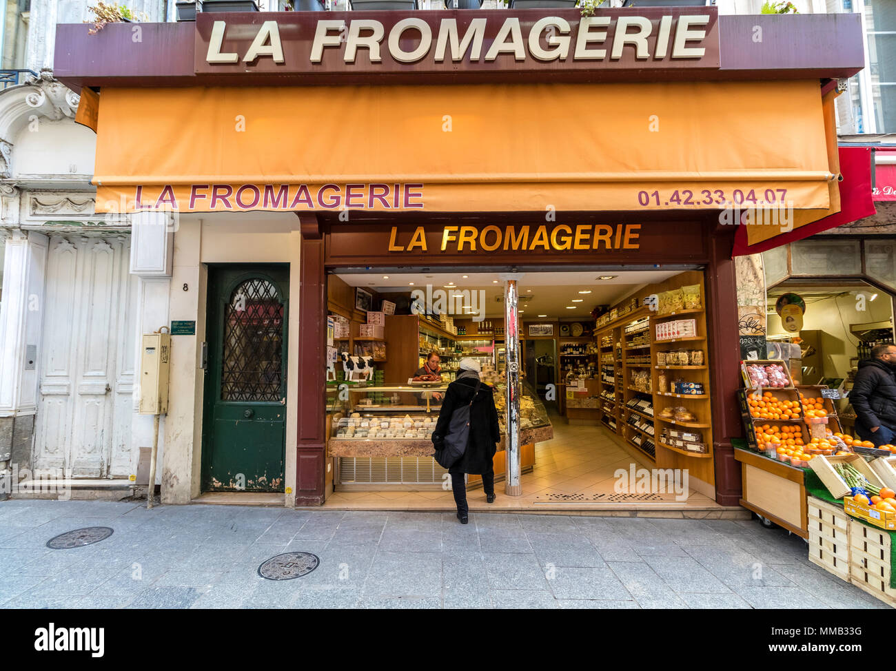 A woman looking in the window of a cheese shop ,La Fromagerie on Rue Montorgueil ,Paris ,France - Stock Image