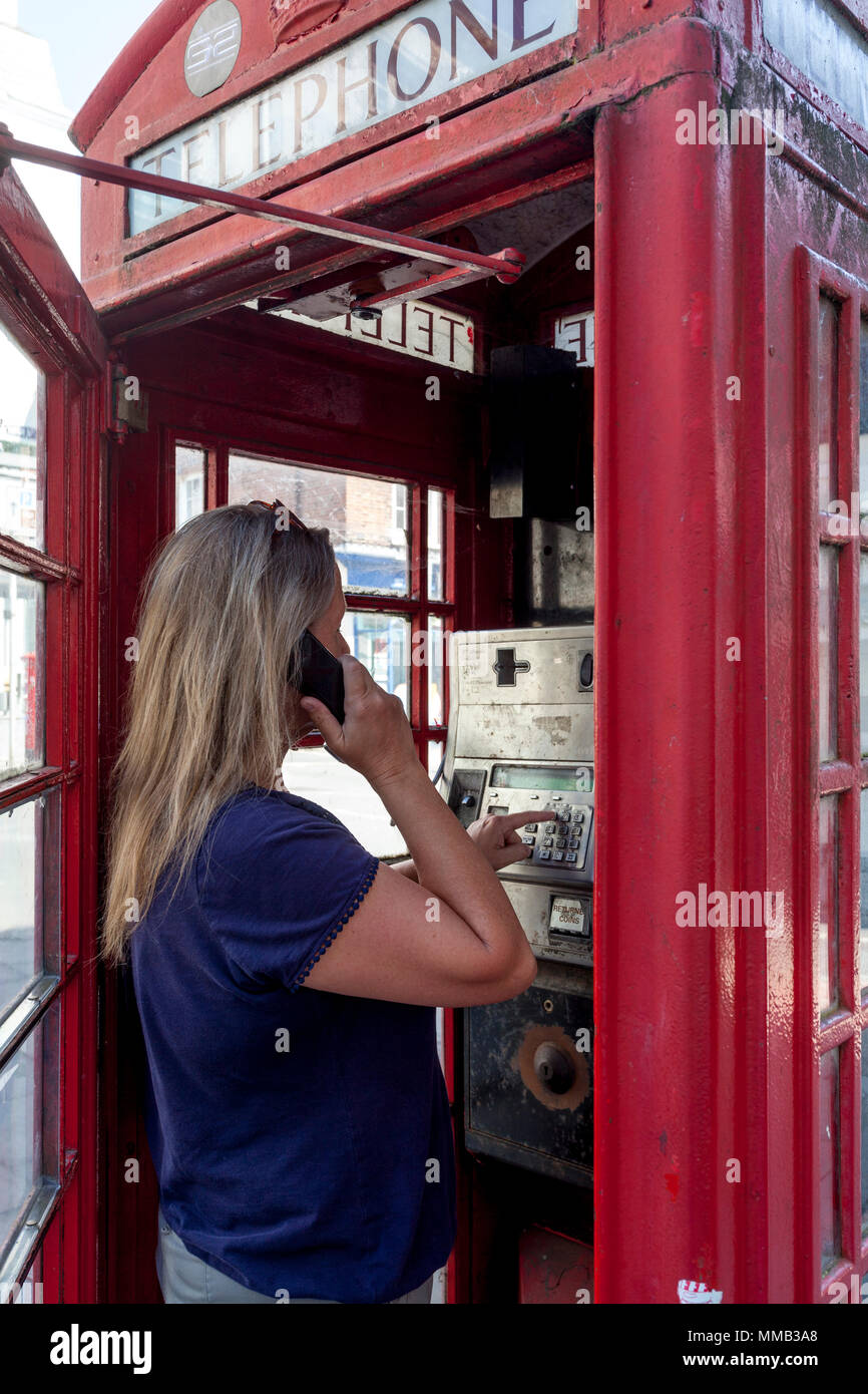 A Woman Using A Traditional Red Telephone Box, Sussex, England - Stock Image
