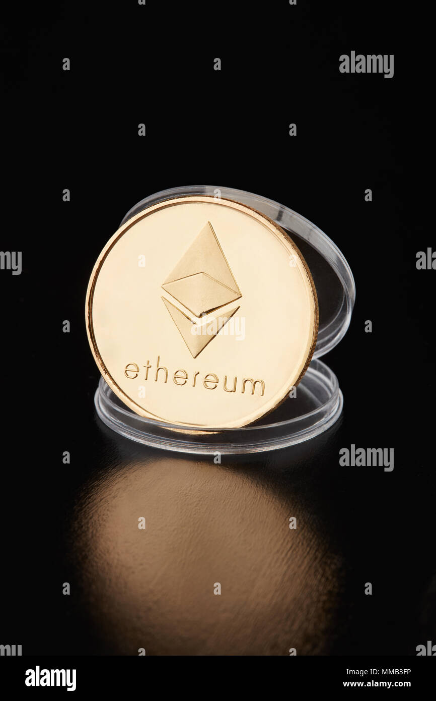 Ethereum golden coin in transparent coin container on black background, clipping path - Stock Image