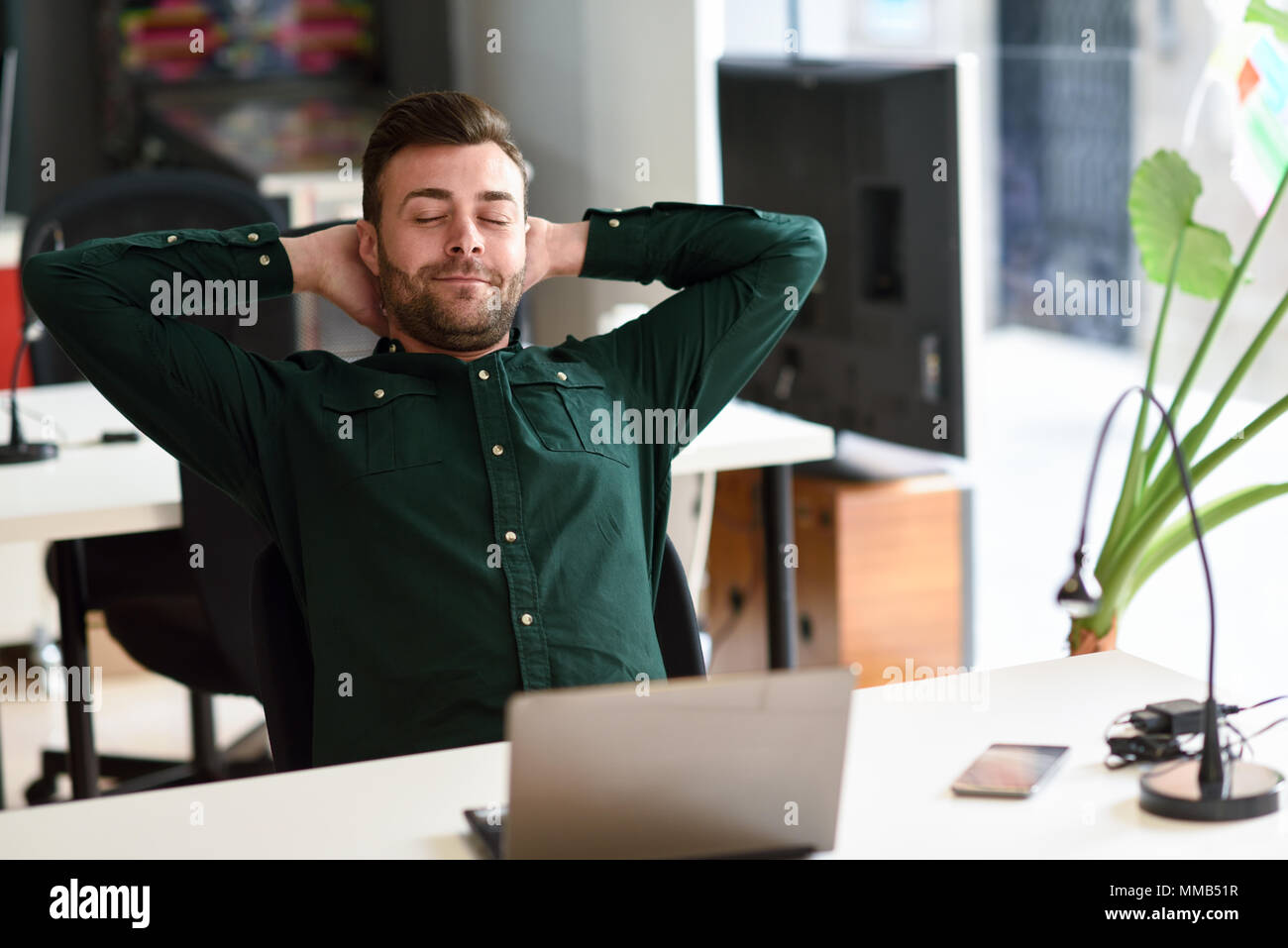 Young man studying with laptop computer on white desk. Attractive guy with beard wearing casual clothes taking a break. - Stock Image