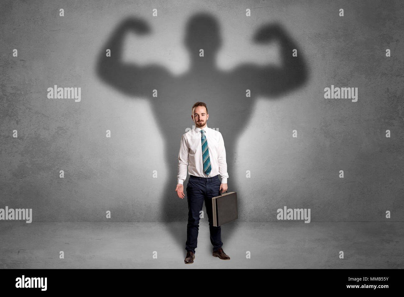 Lovely serious businessman standing with a muscular powerful shadow behind his back  - Stock Image