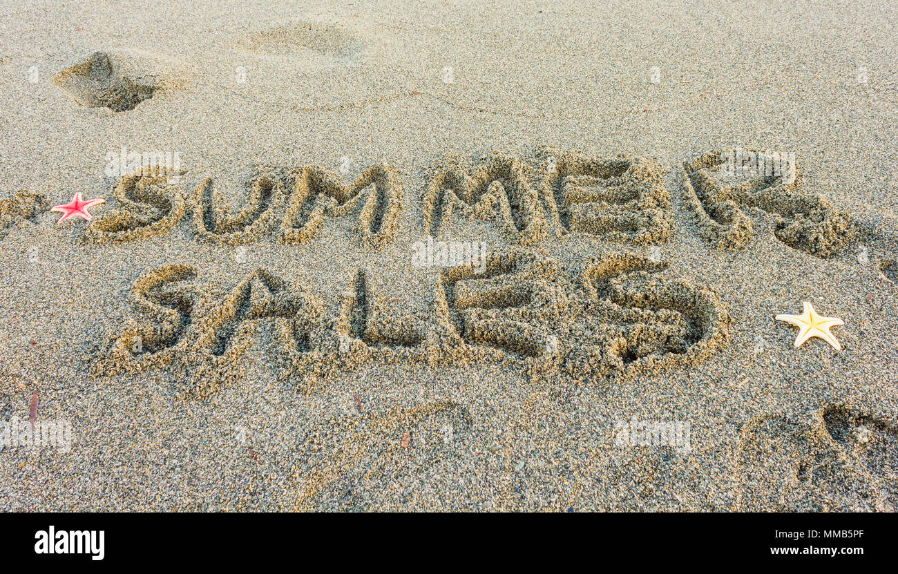 the word summer sales written on the sand - Stock Image