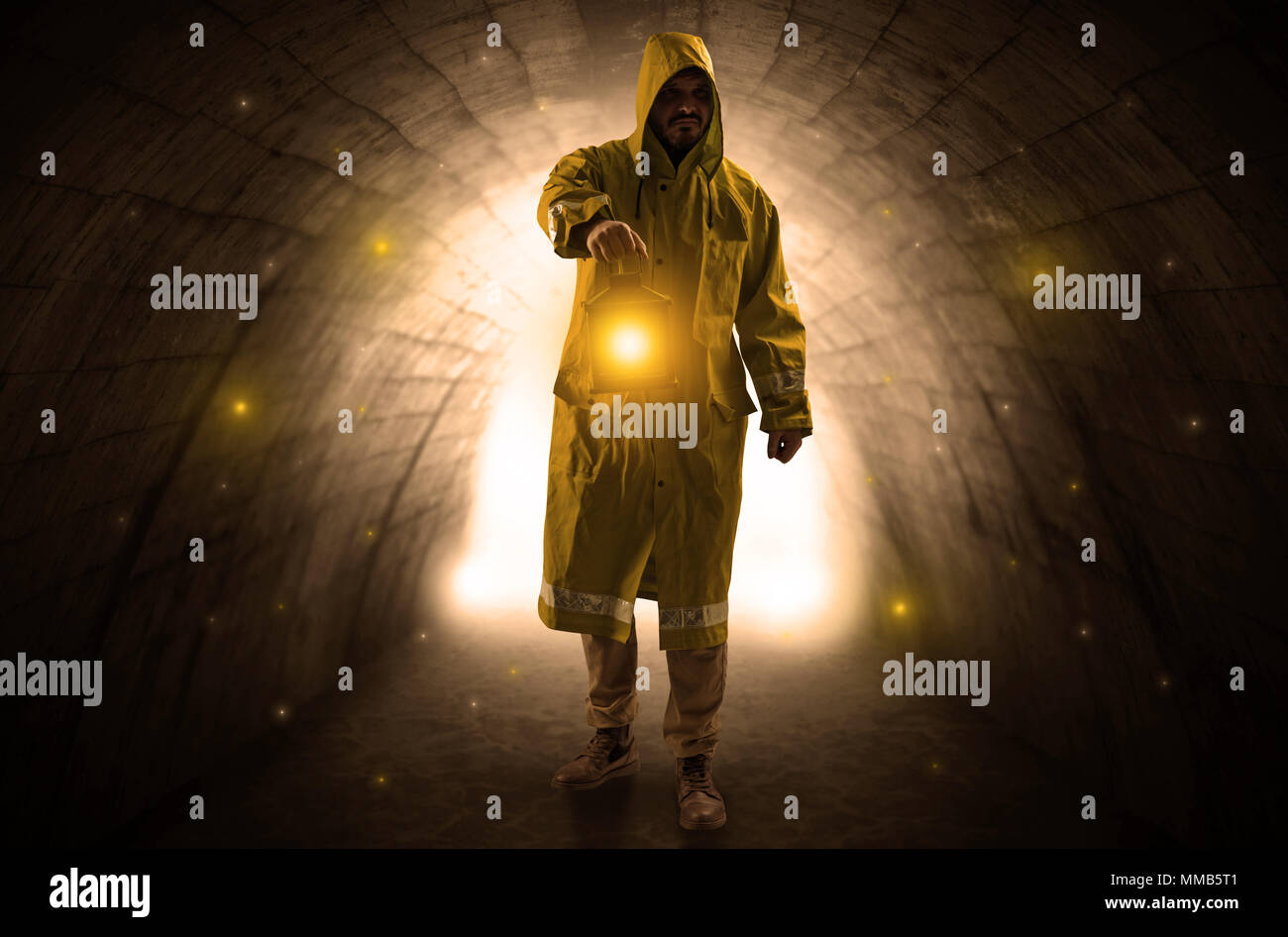 Ugly man in raincoat walking with glowing lantern in a dark tunnel Stock Photo