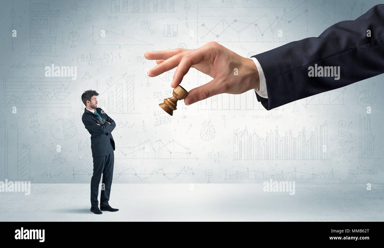 Little businessman is afraid to make the next step in his chess game with graphs, charts and reports background  - Stock Image