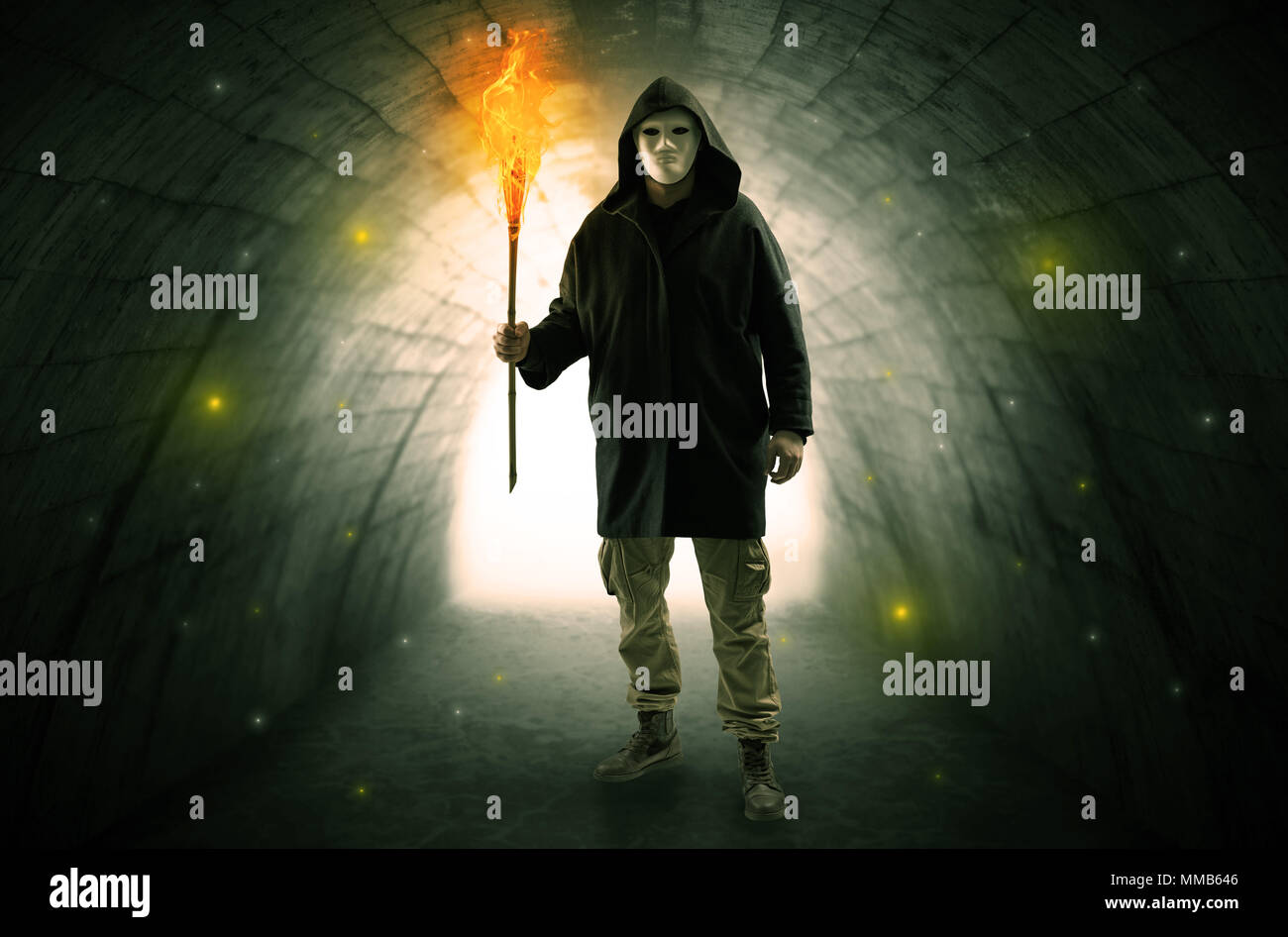 Ugly man with burning flambeau walking in a dark tunnel Stock Photo