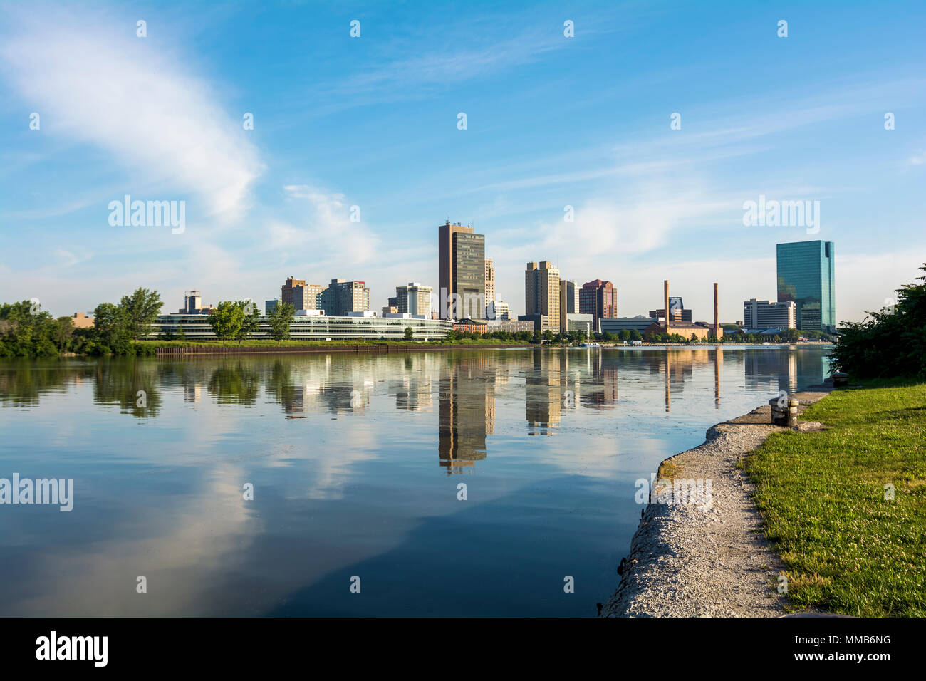 A panoramic view of downtown Toledo Ohio's skyline from across the Maumee River.  A beautiful blue sky with white clouds reflecting into the water. Stock Photo