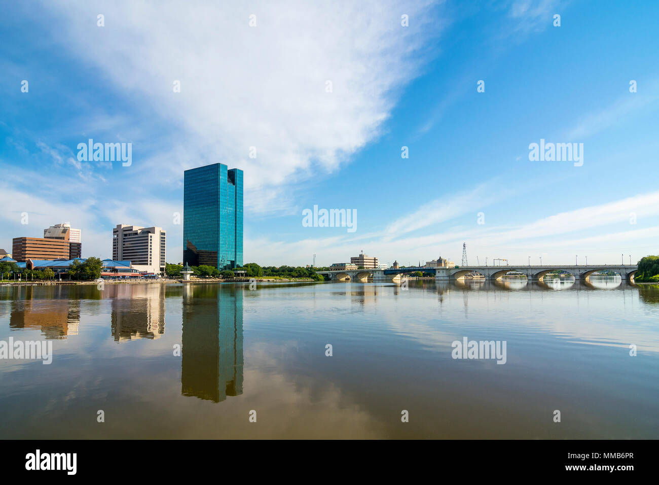 A panoramic view of downtown Toledo Ohio's skyline reflecting into the Maumee River.  A beautiful  blue sky with white clouds for a backdrop. Stock Photo
