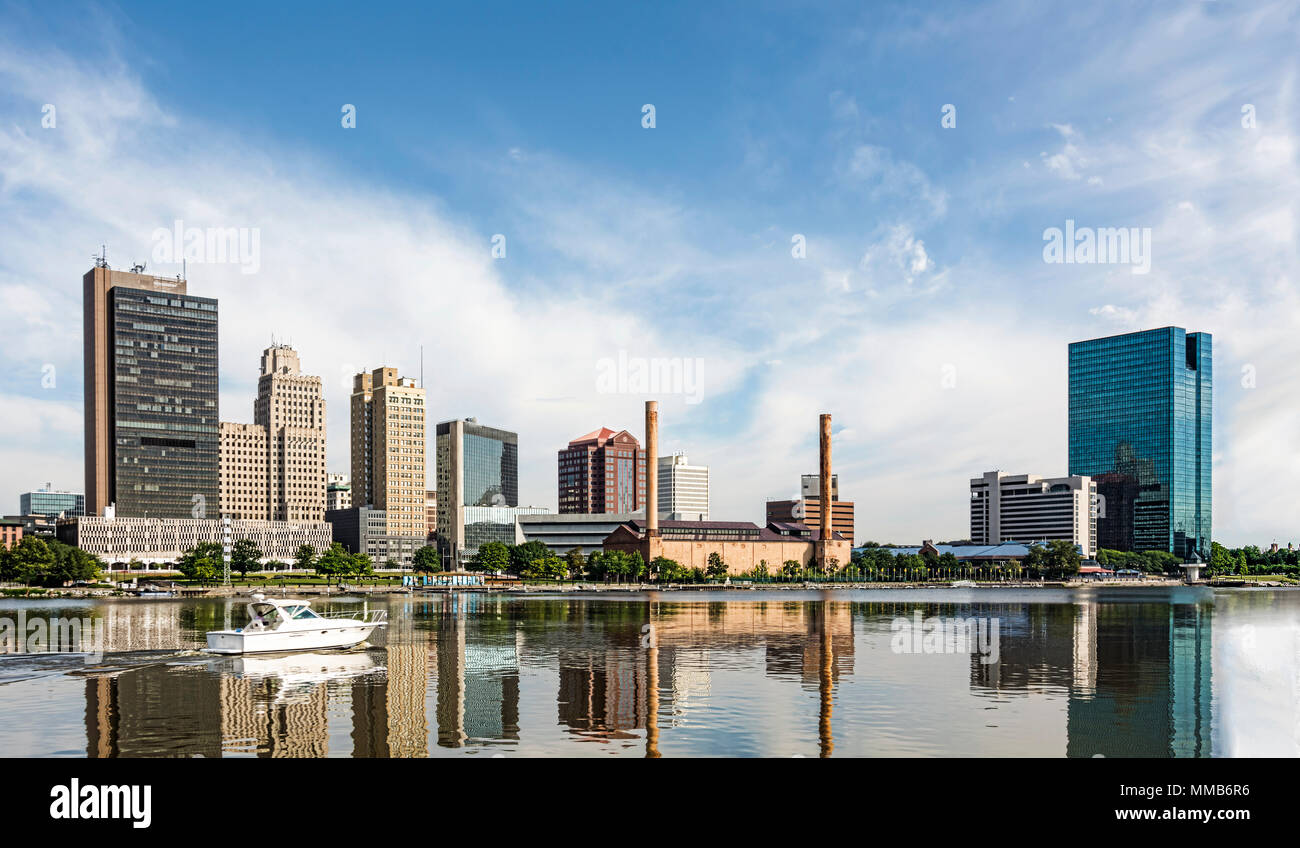 A panoramic view of downtown Toledo Ohio's skyline reflecting into the Maumee River with a power boat cruising by.  A beautiful  blue sky. Stock Photo