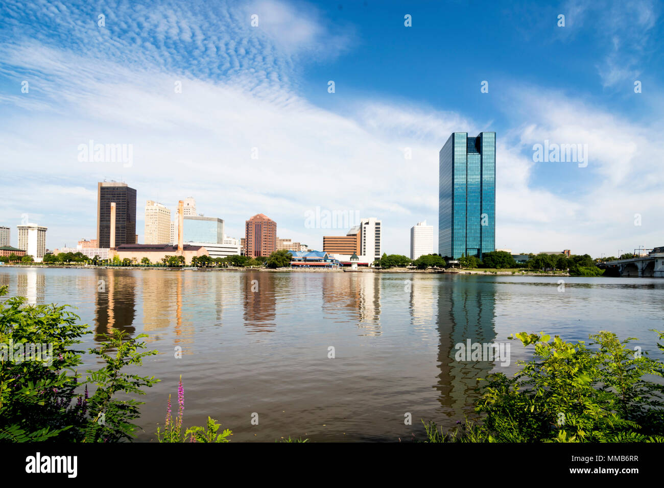 A panoramic view of downtown Toledo Ohio's skyline from across the  Maumee River.  A beautiful  blue sky with white clouds for a backdrop. Stock Photo