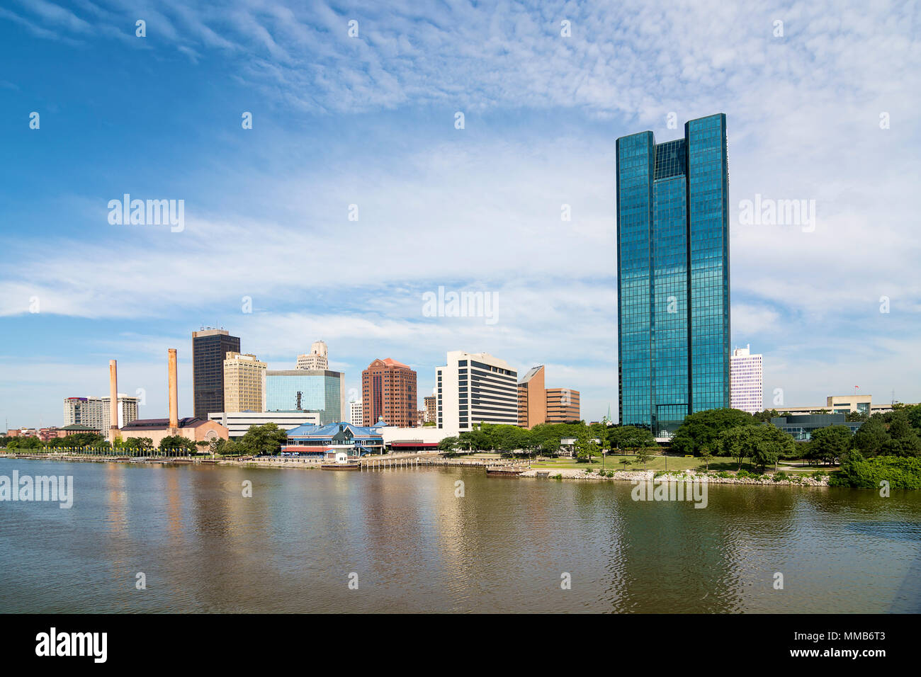 A panoramic view of downtown Toledo Ohio's skyline and the Maumee river.  A beautiful  blue sky with white clouds for a backdrop. Stock Photo