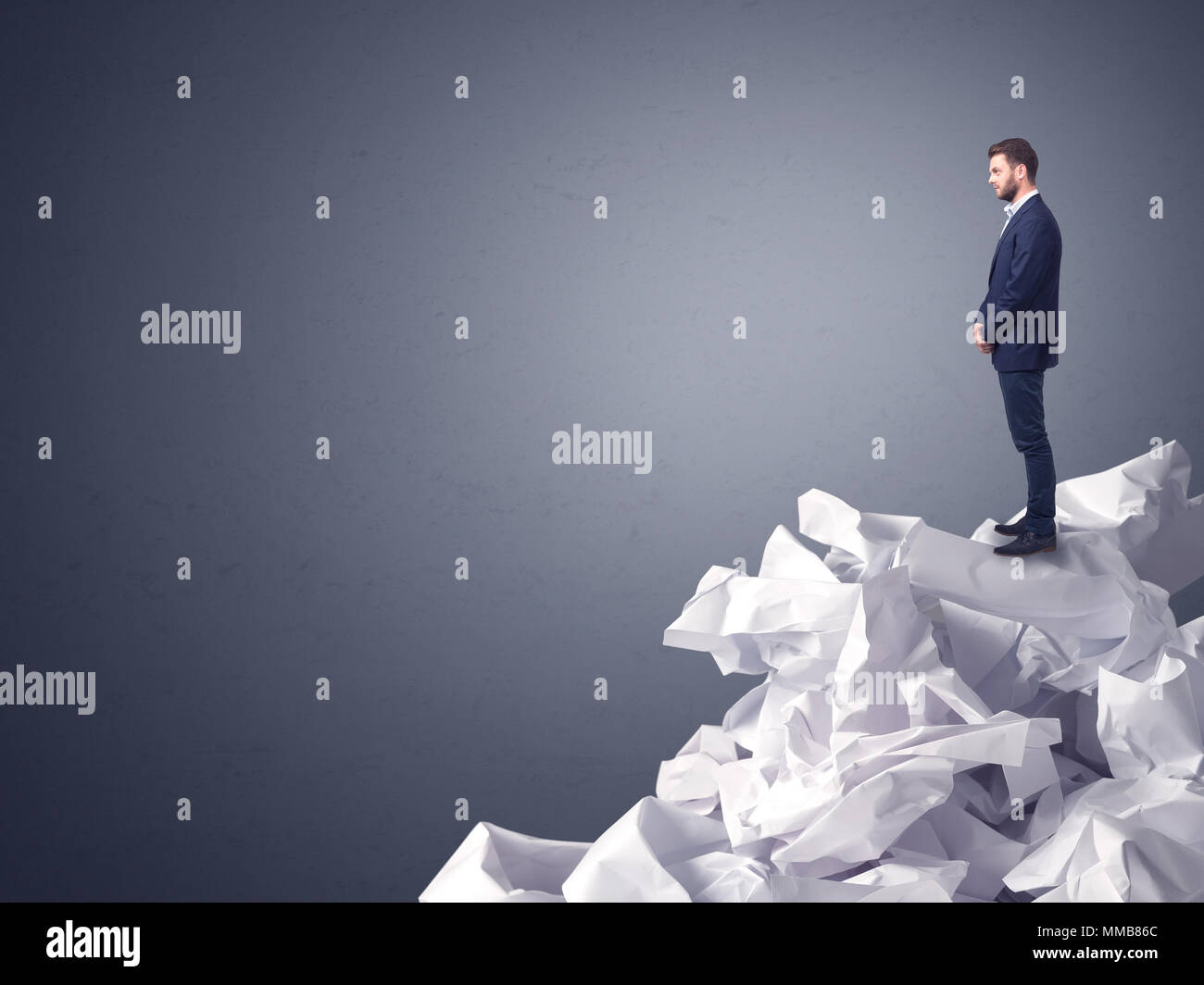Thoughtful young businessman standing on a pile of crumpled paper with a dark grey background Stock Photo