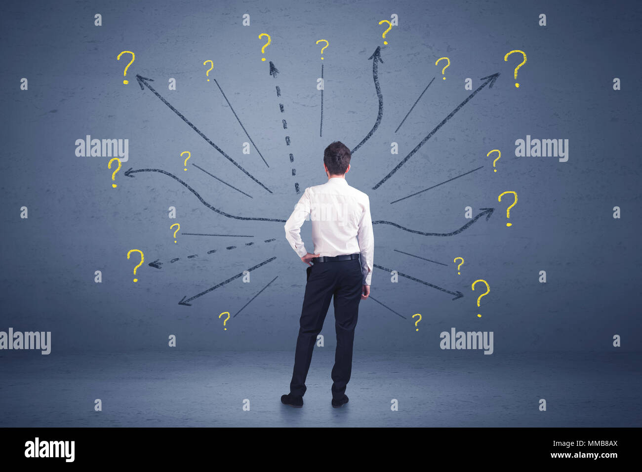 Businessman standing in front lines and question mark signs concept on background Stock Photo