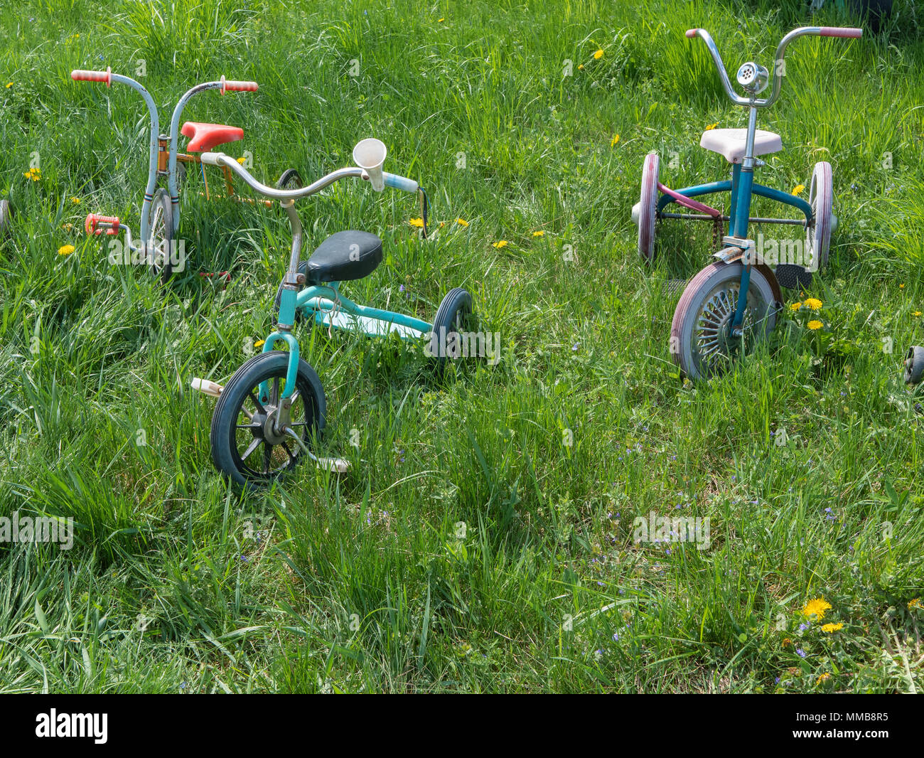 Three Old Vintage Retro Child Baby Tricycles Three Wheels Bikes On A Green Grass At Shiny Summer Day Stock Photo Alamy