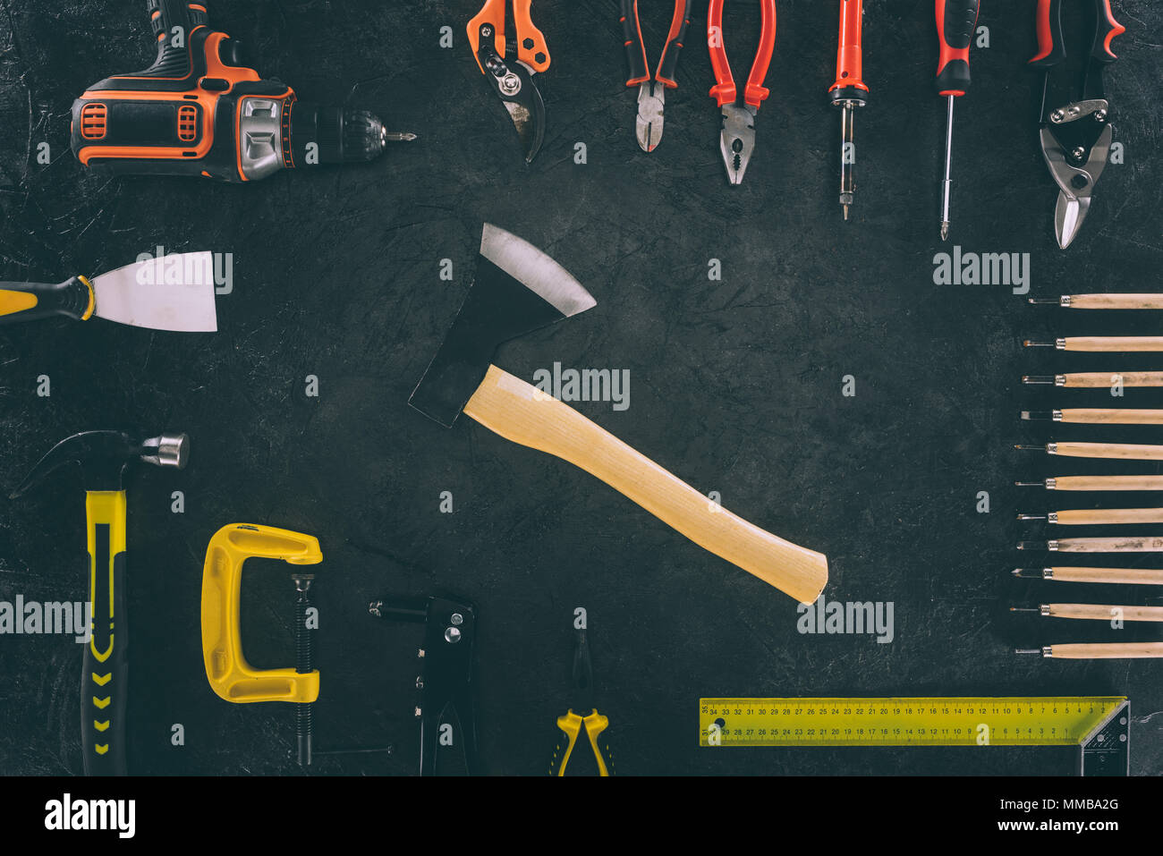 flat lay with axe and various arranged carpentry equipment on dark surface Stock Photo