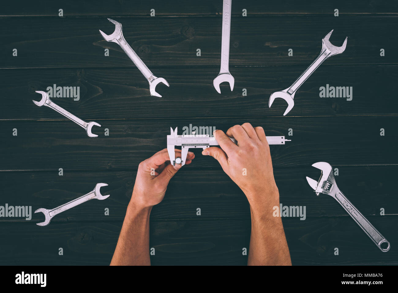 cropped shot of worker getting measurements with vernier caliper and wrenches on wooden tabletop - Stock Image