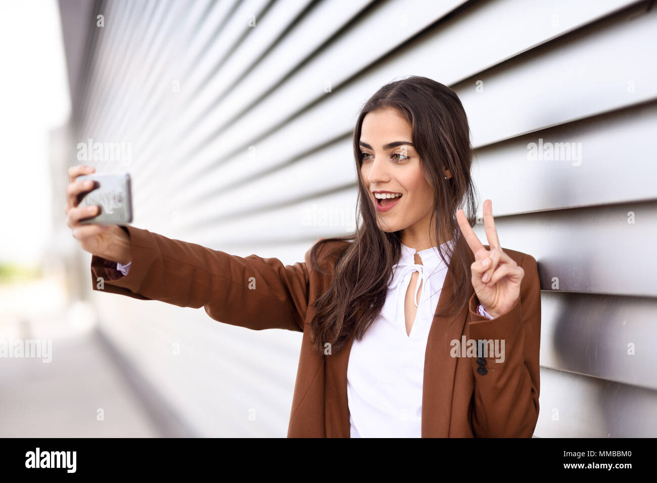 Young woman taking selfie photograph with smartphone in urban background. Beautiful girl wearing formal wear using smart phone. Young female with brow - Stock Image