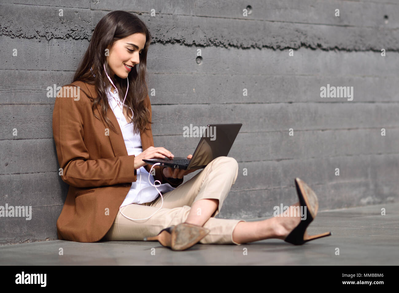 Young businesswoman sitting on floor looking at her laptop computer. Beautiful woman wearing formal wear using earphones. - Stock Image