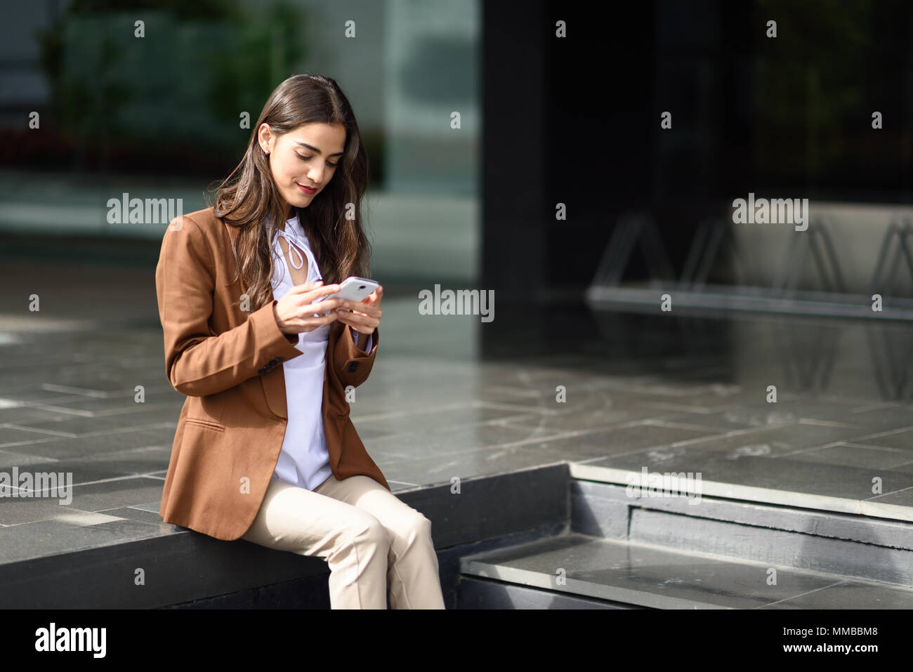 Young businesswoman texting with a smartphone next to an office building. Beautiful woman wearing formal wear using smart phone. Young girl with brown - Stock Image