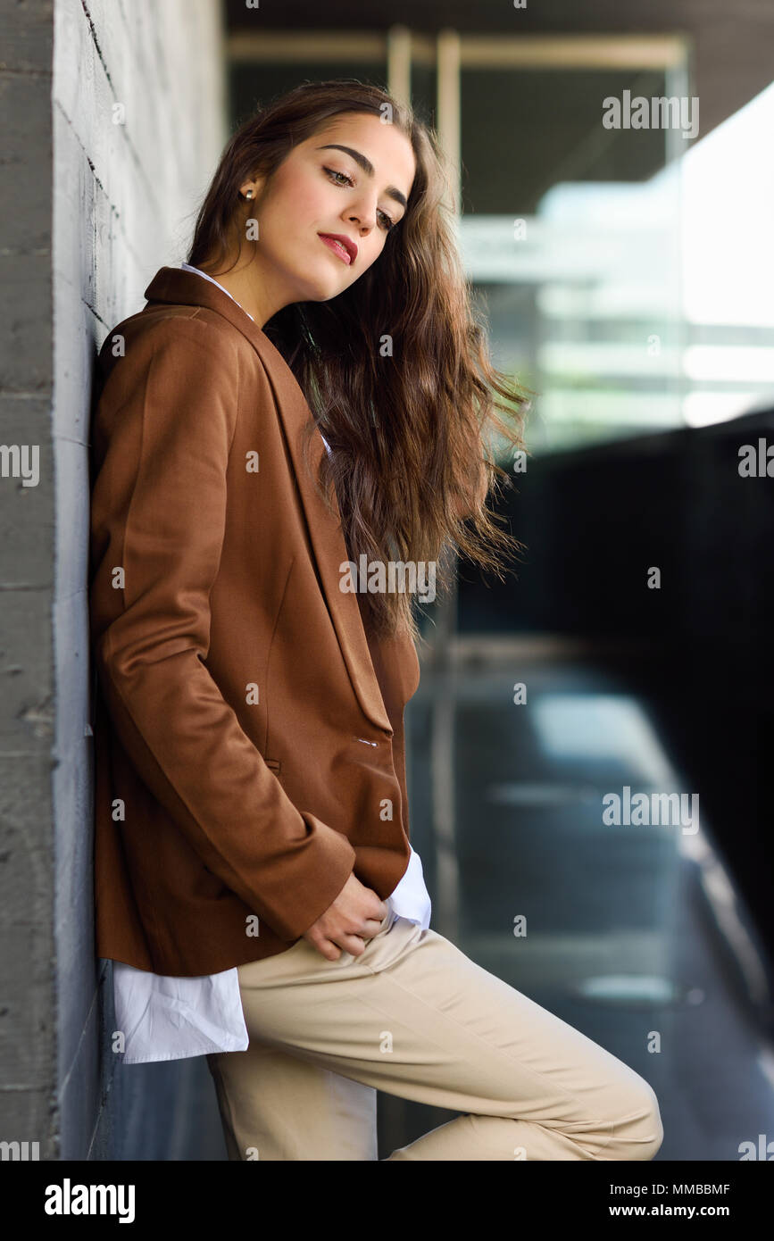 Young woman with nice wavy long hair. Beautiful girl wearing formal wear. Young female with brown jacket. - Stock Image