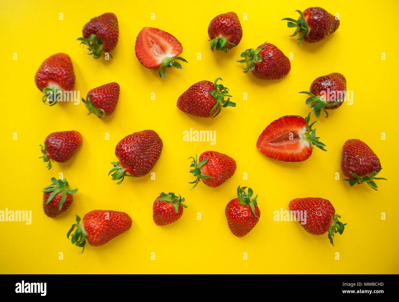 Red juicy strawberries on bright yellow background. - Stock Image