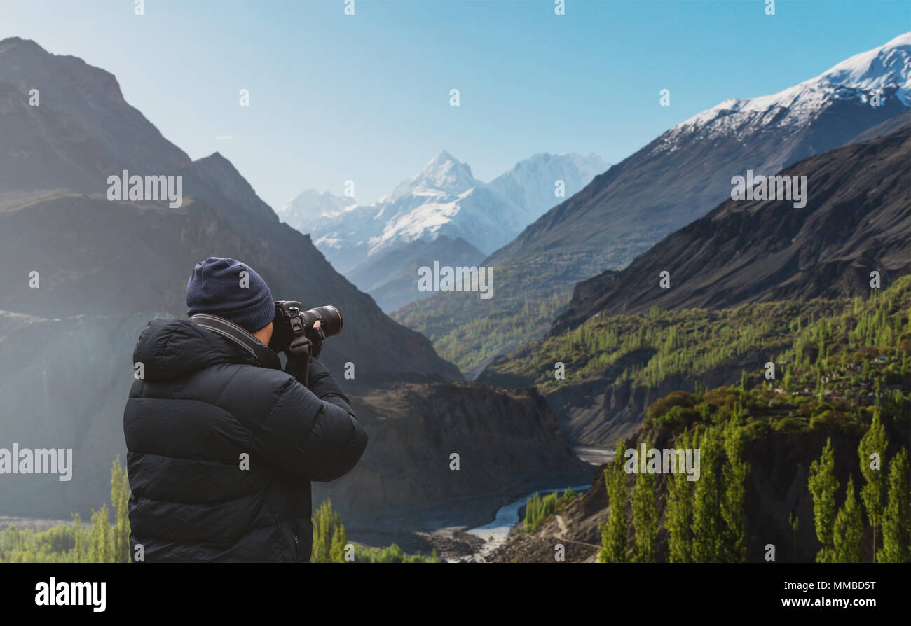 Photographer taking photograph of Hunza valley landscape in Pakistan by dslr camera - Stock Image