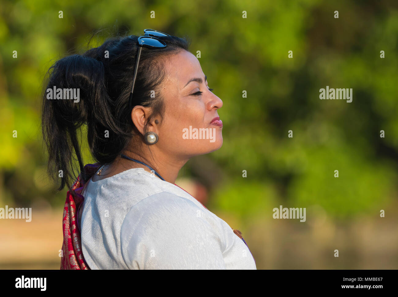Pretty middle aged Asian woman in the UK standing outside, taking in a deep breath of fresh outdoors air. Taking it in concept. - Stock Image