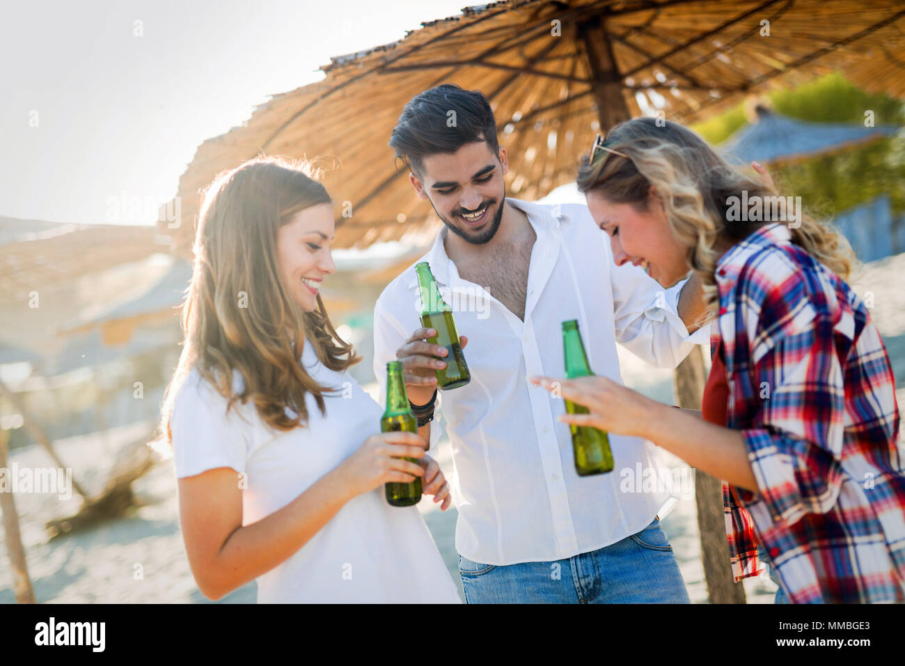 Beach party with friends. Cheerful young people spending nice time together on the beach - Stock Image