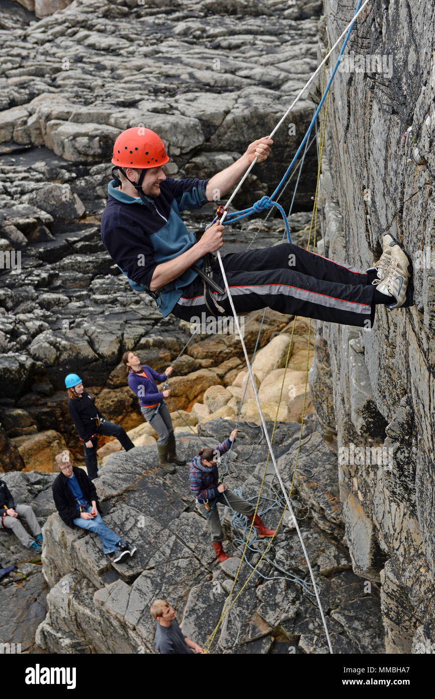 Climbers club climbing and abseiling on cliffs next to the sea. A variety of young and old participants Stock Photo