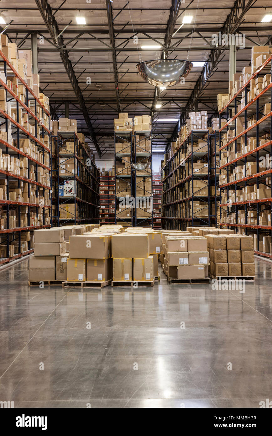View down aisles of racks holding cardboard boxes of product on pallets  in a large distribution warehouse - Stock Image
