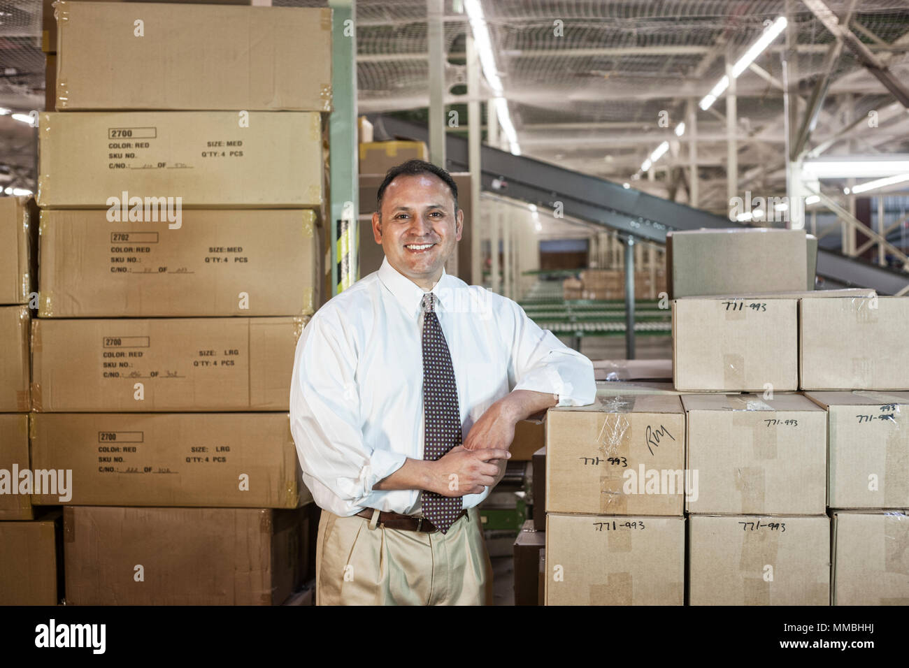 Portrait of a male Hispanic American executive in a shirt and tie surrounded by products stored in cardboard boxes  in a large distribution warehouse. - Stock Image