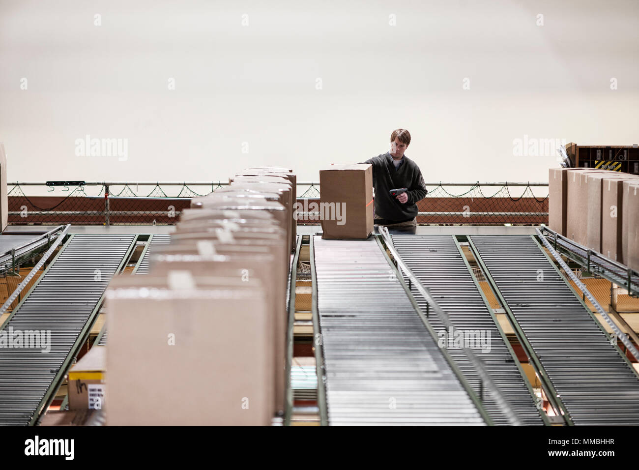 Causcasian warehouse worker in a large distribution warehouse, showing products stored in cardboard boxes, and moving on a motorized converyor system. - Stock Image