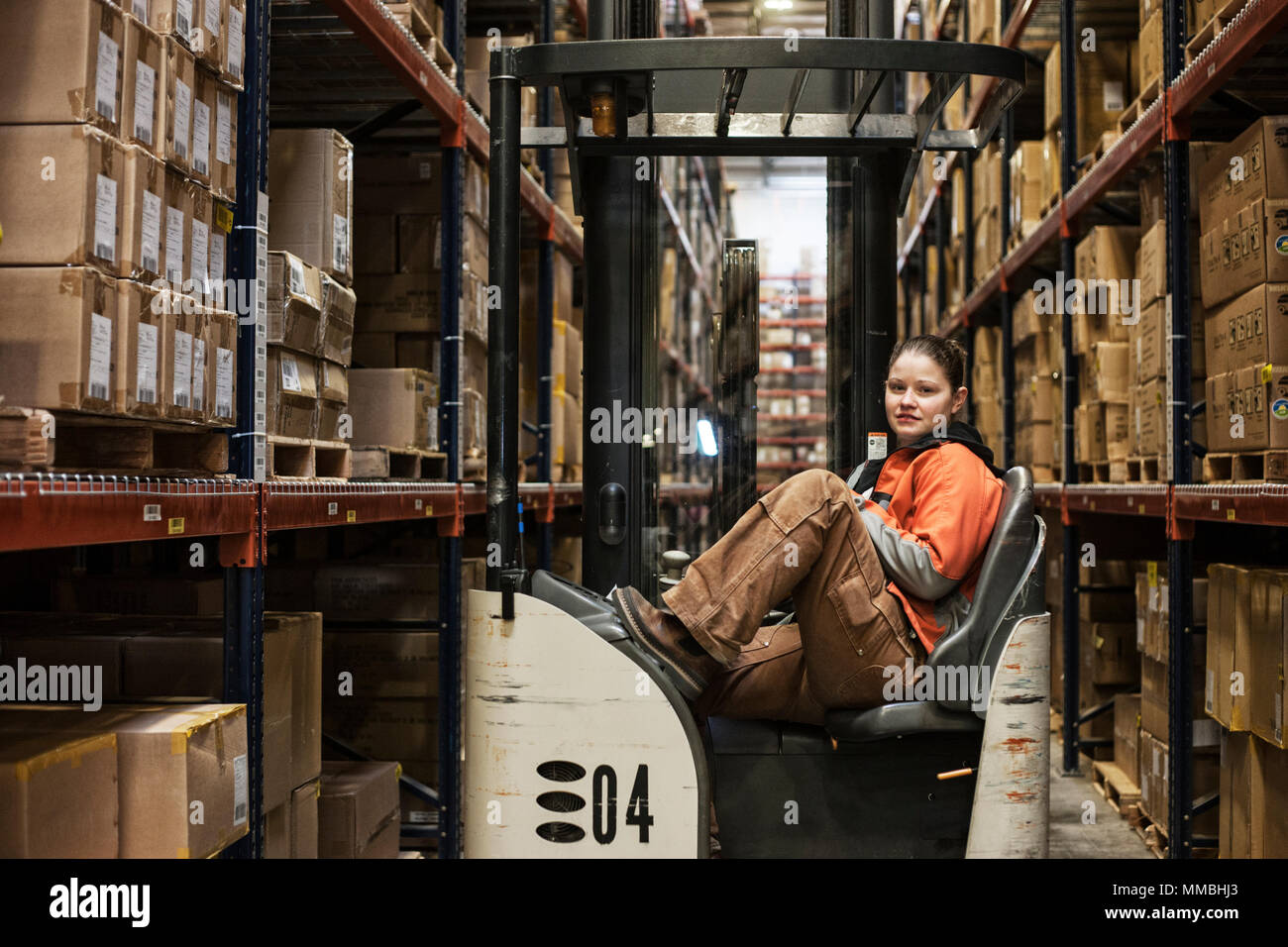 Caucasian female warehouse worker sitting in a motorized stock picker surrounded by products stored in cardboard boxes in a large warehouse distributi - Stock Image