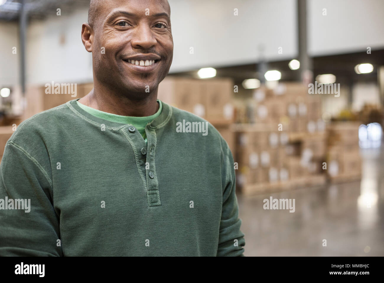 Portrait of an African American warehouse worker in a large distribution warehouse - Stock Image