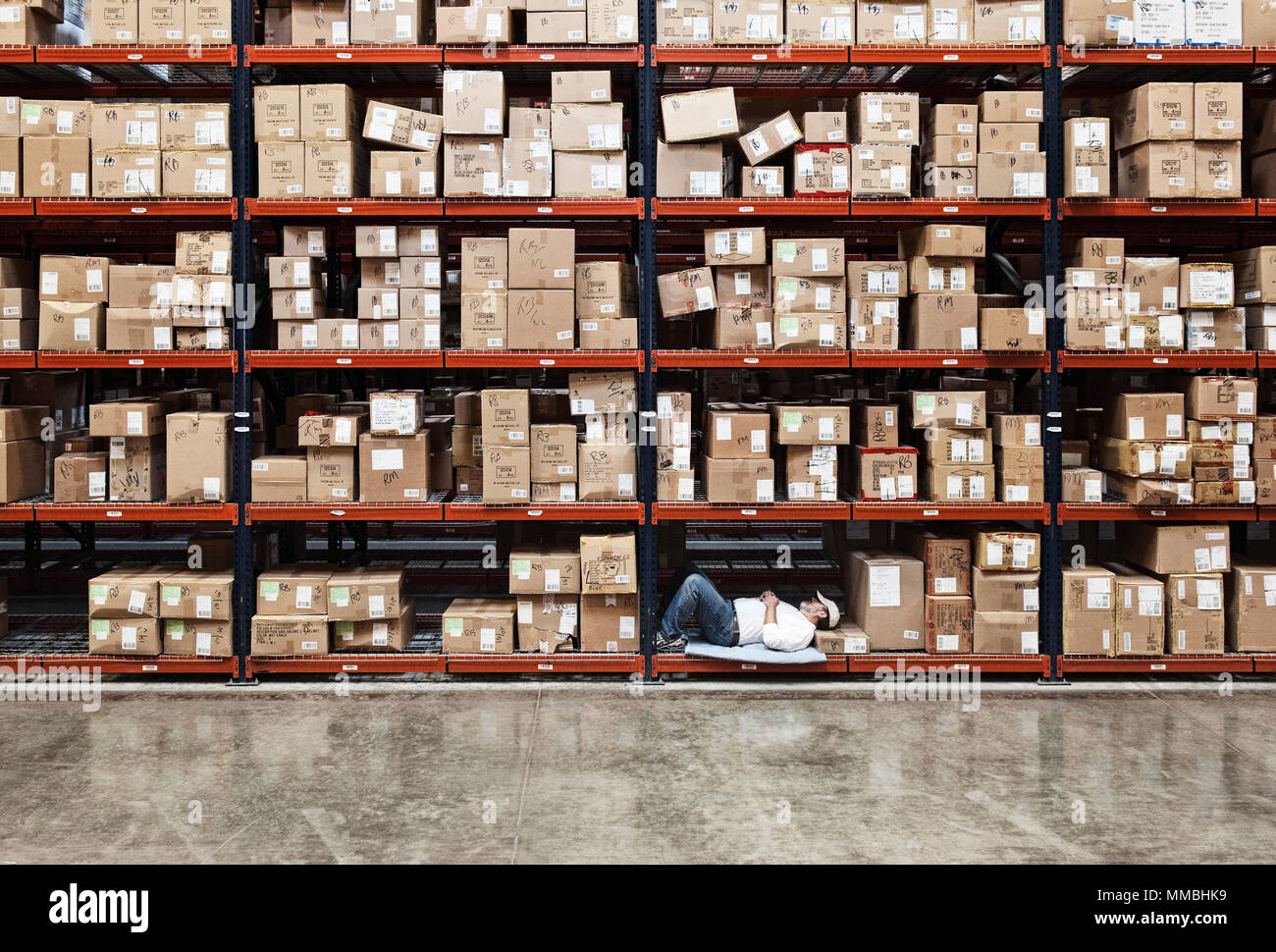 Warehouse worker taking a break next to large racks of cardboard boxes holding product in a distribution warehouse. - Stock Image